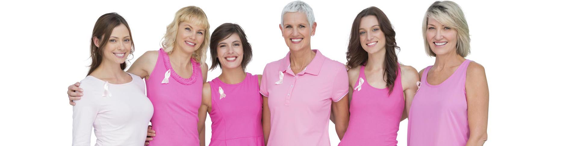 Smiling women wearing pink for breast cancer awareness on white background